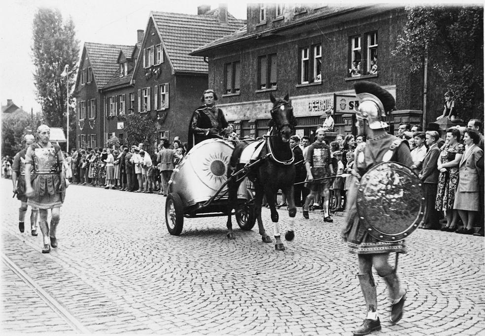 zu sehen ist die ein altes Foto vom Umzug anlässlich der 1.000 Jahr Feier mit römischen Soldaten und einem Einspänner