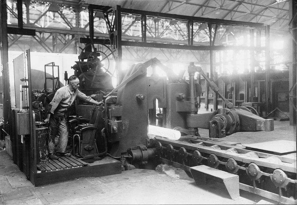 zu sehen ist eine Maschine und ein gluehend heißer Stahlblock im frueheren Bouser Werk