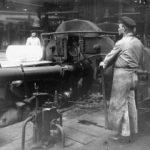 zu sehen ist auf diesem alten Foto die Einfuhr eines dicken gluehenden Stahlblocks zur Weiterverarbeitung
