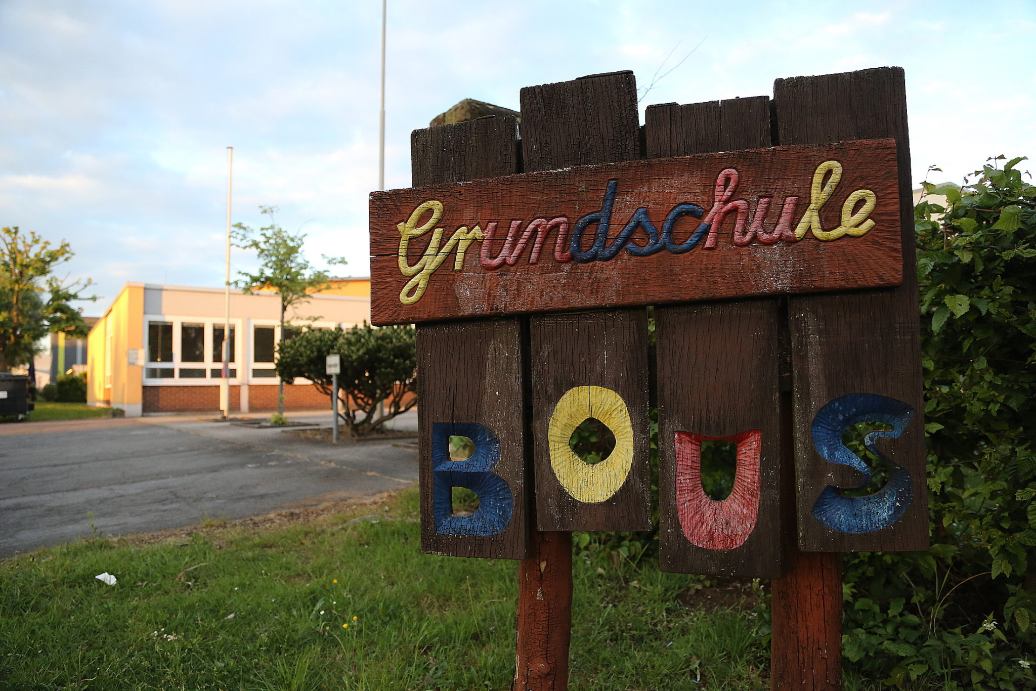 zu sehen ist das bunte Holzschild der Grundschule Bous