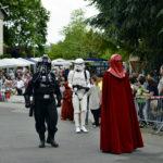 zu sehen sind mehrere Figuren aus dem Film Star Wars in originalgetreuen Masken und Kleidern bei einem Umzug anlaesslich der Bouser Maisause