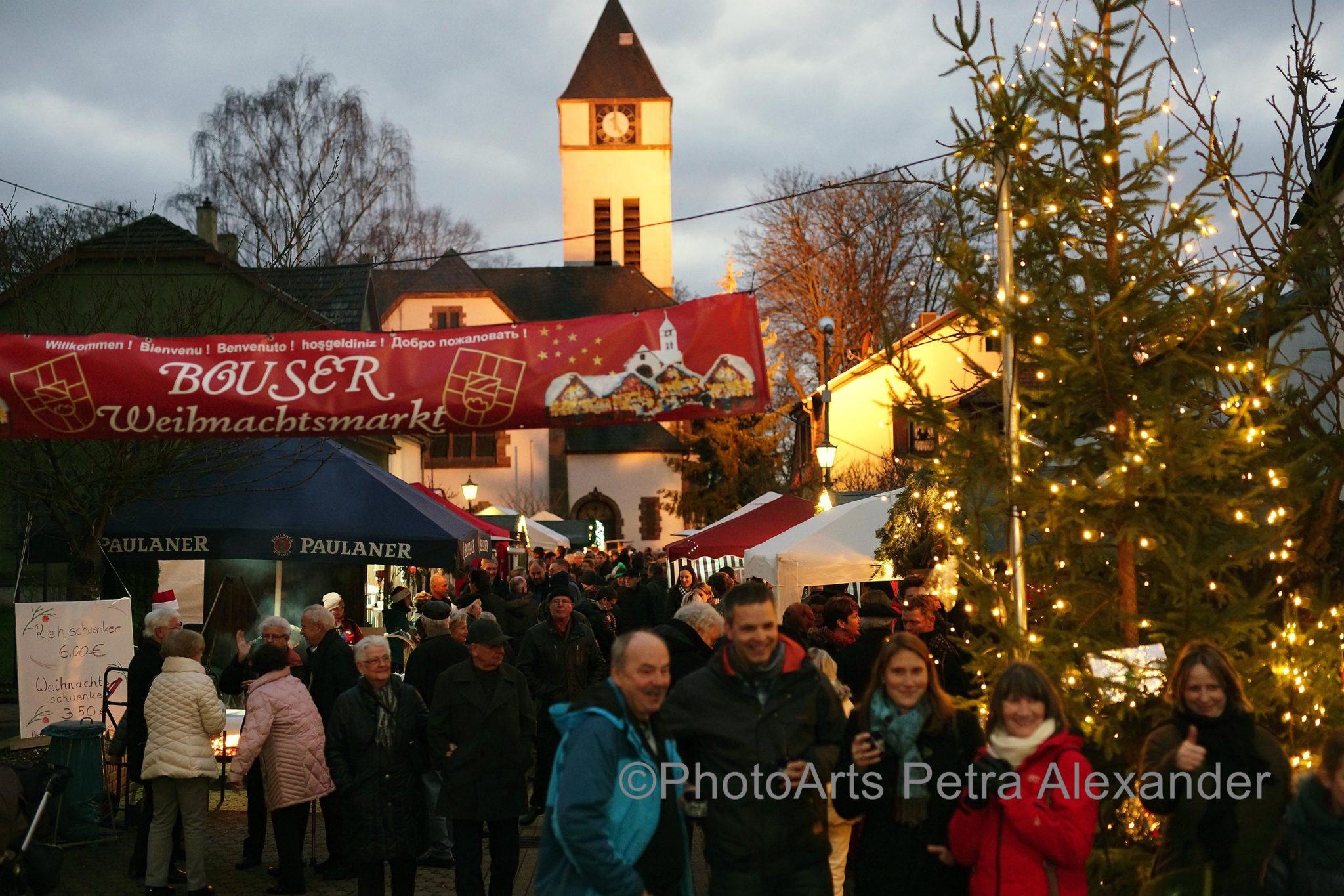 zu sehen ist der Eingangsbereich des Weihnachtsmarktes mit vielen Menschen und bunten Lichtern