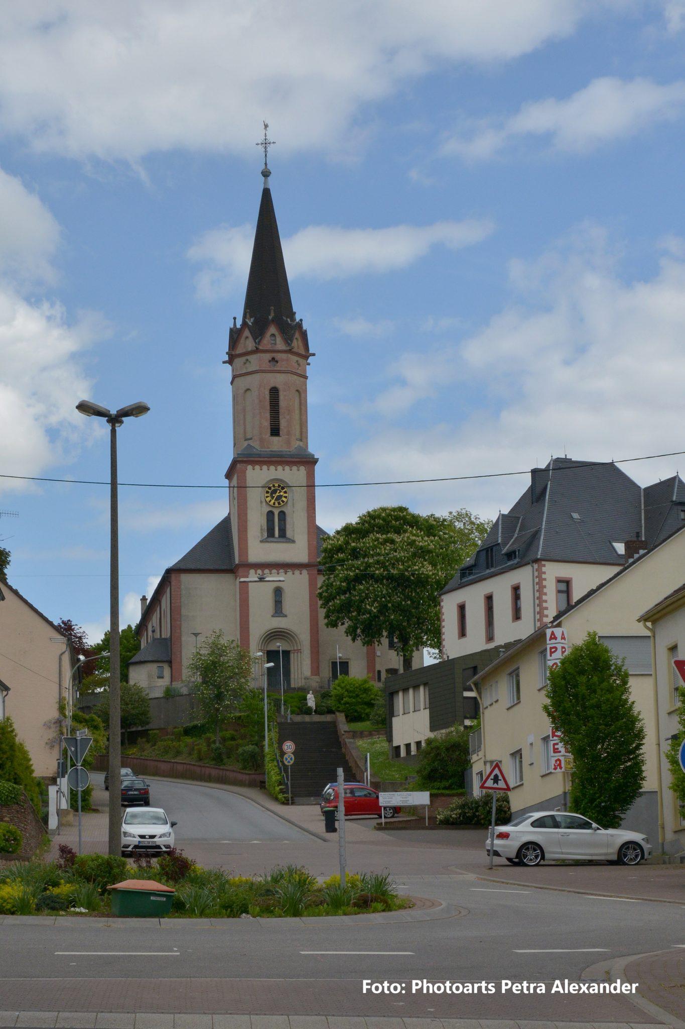 zu sehen ist die Katholische Kirche mit Treppenaufgang aus Sicht des Kreisverkehrs