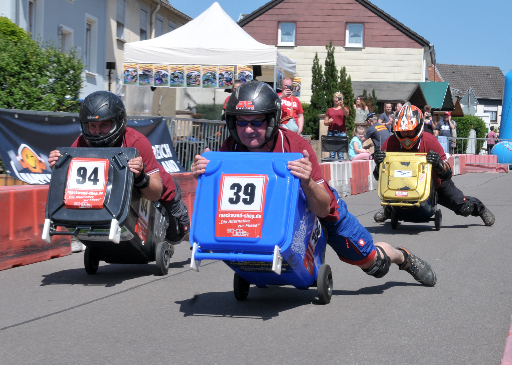 zu sehen sind drei Fahrer beim Muelltonnenrennen an der Bouser Maisause. Die Fahrer liegen auf den Tonnen, heben sie an und rollen auf den zwei Raedern die Rennstrecke hinunter.