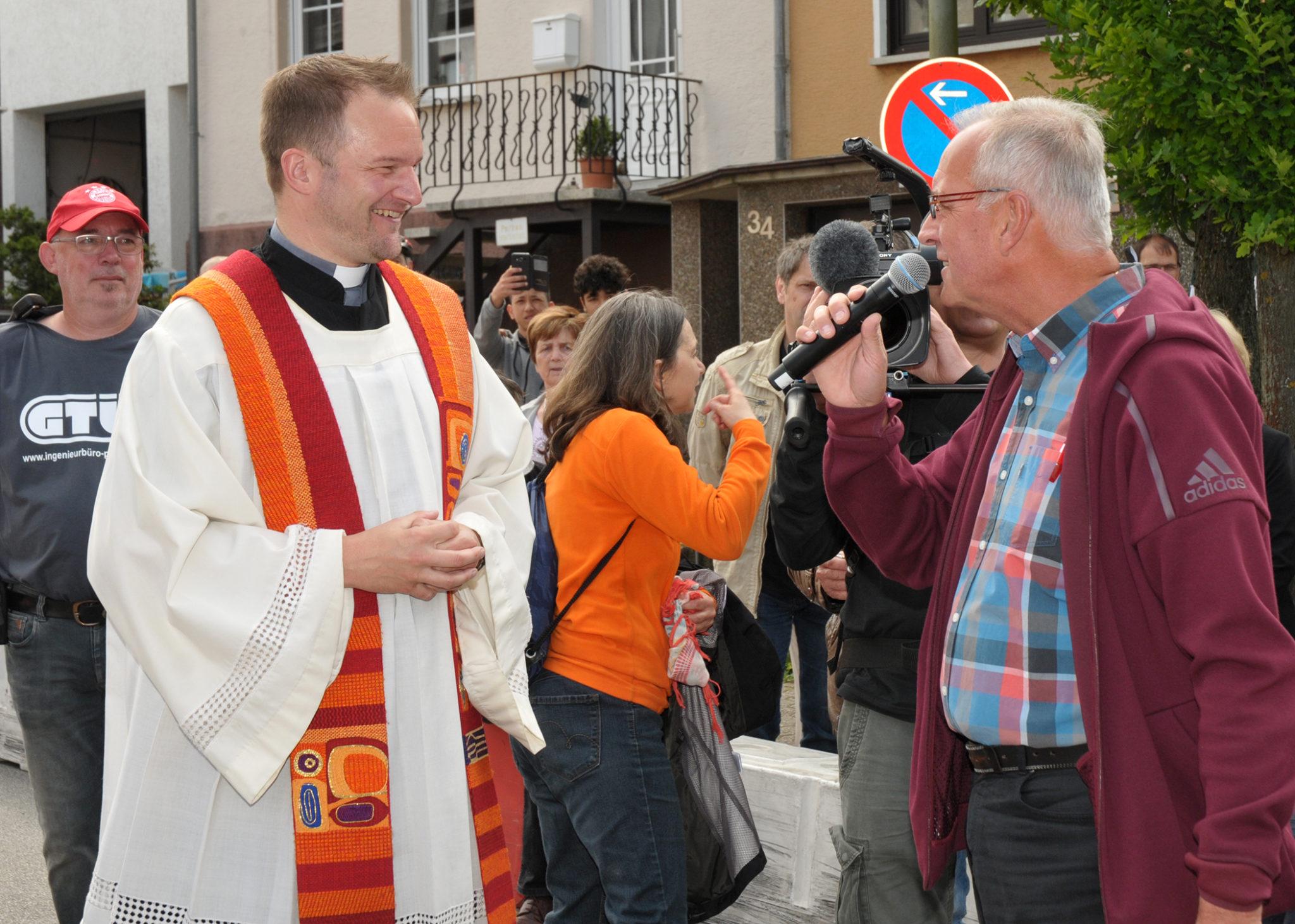 zu sehen ist Moderator Thomas Wollscheid im Interview mit Pastor Dr. Frank Kleinjohann. Im Hintergrund das Filmteam des Saarländischen Rundfunks