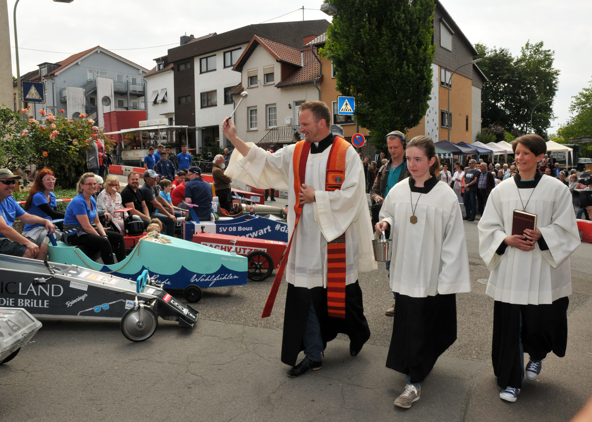 zu sehen sind zwei Messdiener und Pastor Dr. Frank Kleinjohann beim segnen der Seifenkisten nach dem Hochamt