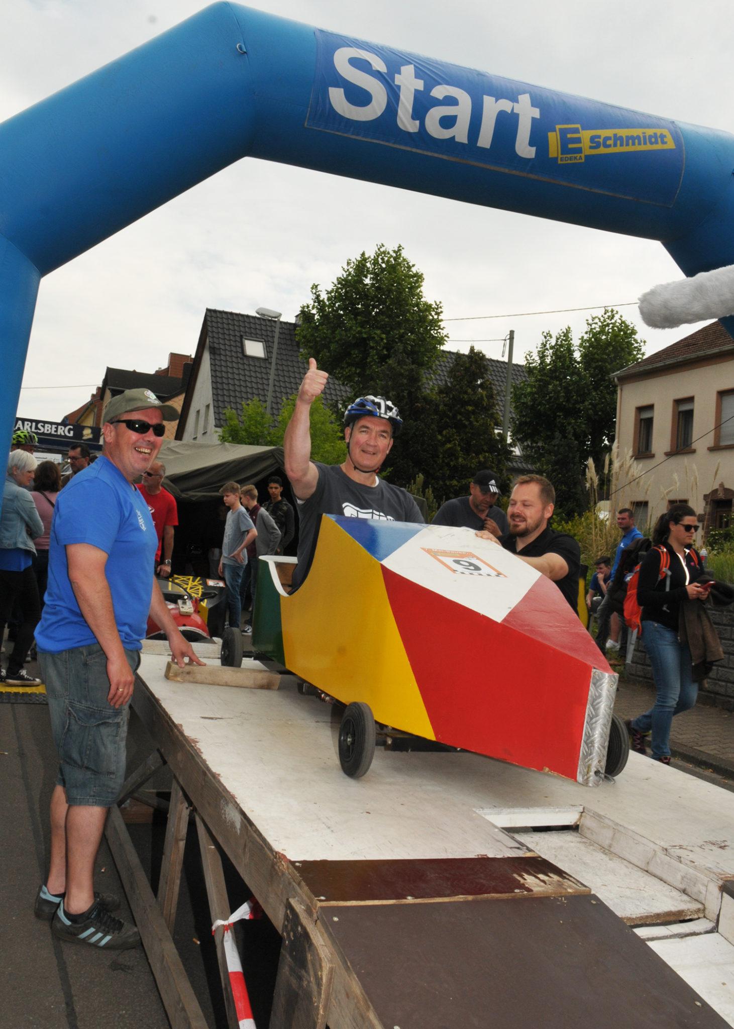 zu sehen ist Bürgermeister Stefan Louis in der Seifenkiste des Partnerschaftsvereins auf der Startrampe, kurz vor dem Start des Prominentenrennens an der Bouser Maisause