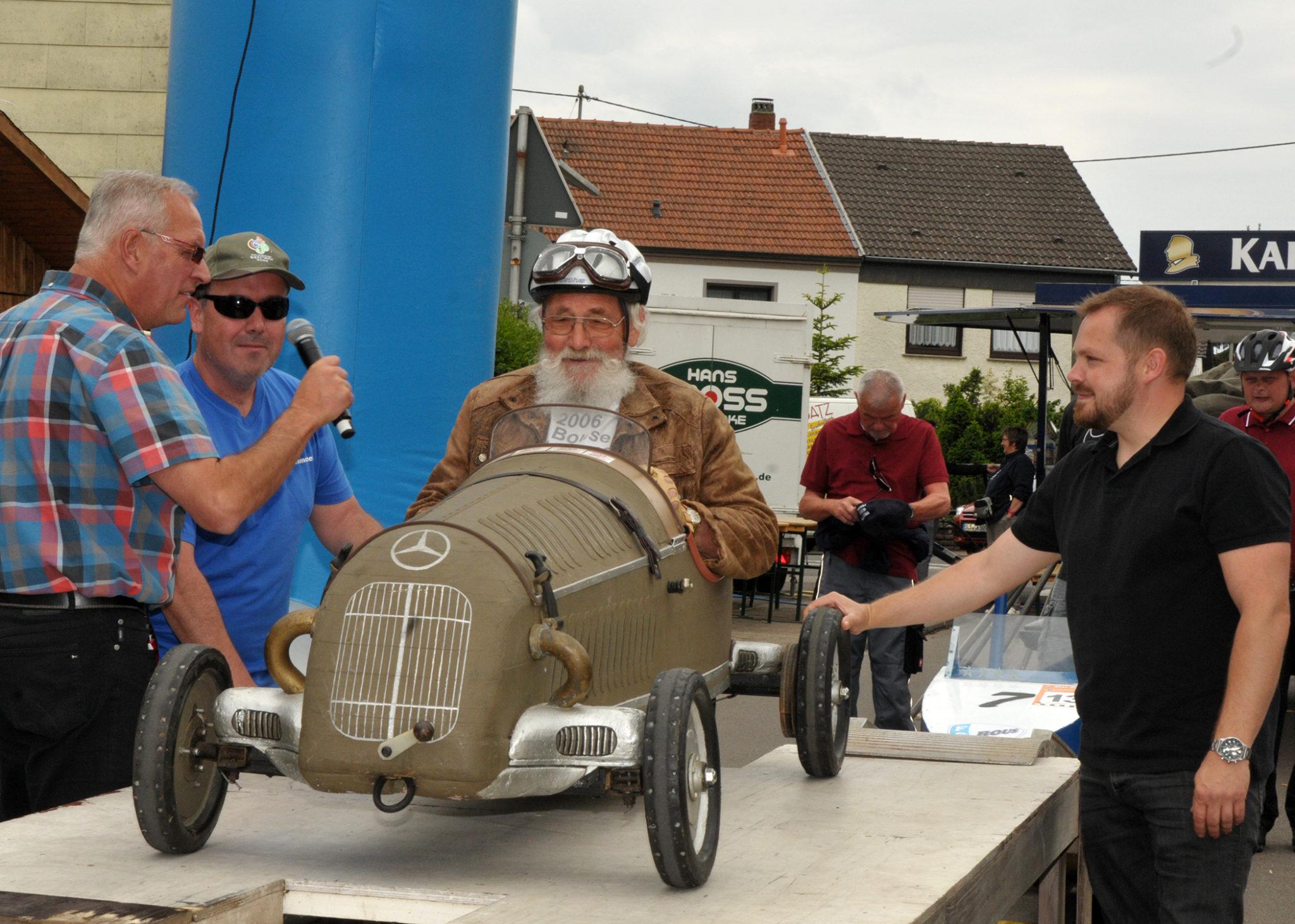 zu sehen ist der Bouser Alfred Geber mit seinem alten Mercedes-Nachbau beim Start der Bouser Maisause