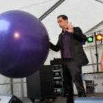 zu sehen ist der Zauberer Maxime Maurice auf der Maisausenbühne mit einem riesigen Ballon