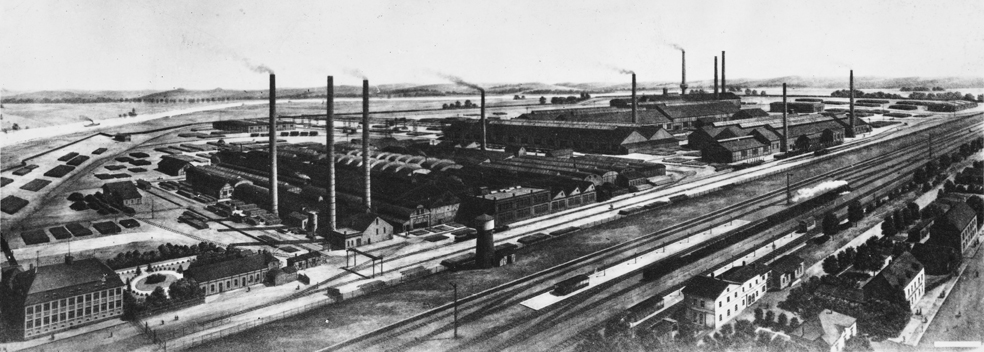 zu sehen ist ein sehr altes Foto der Roehrenwerke Bous, im Vordergrund ist der Bahnhof zu sehen