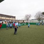 Zu sehen ist das Mini-Sportfeld mit Kunstrasen auf dem Schulhof der Grundschule Bous mit Fußball spielenden Kindern.