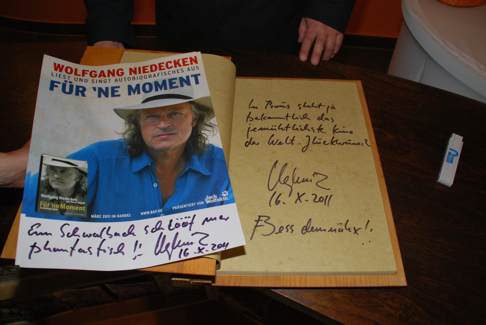 zu sehen ist ein Plakat sowie die Widmung von Wolfgang Niedecken, dem Säenger der Gruppe BAP, im goldenen Buch der Gemeinde Bous.