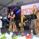zu sehen ist die Band 42komma2 mit Rewe Chef Klaus Fischer in der Mitte