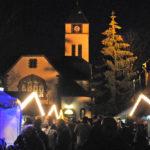 zu sehen sind beleuchtete Weihnachtshütten mit vielen Menschen davor und im Hintergrund die beleuchtete und von innen strahlende evangelische Kirche