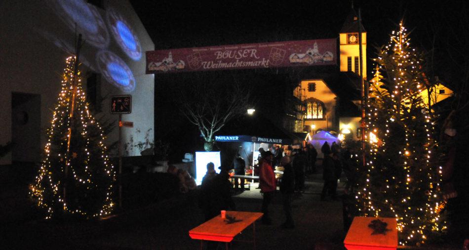 zu sehen ist der beleuchtete Eingang am Weihnachtsmarkt mit zwei Tannenbaeumen links und rechts und der im Hintergrund beleuchteten evangelischen Kirche sowie LED Spots der Bayern Bazis Bous die auf eine Hauswand das Bayern Logo projizieren