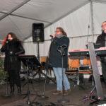 zu sehen sind zwei Musiker und eine Saengerin bei der Live Musik am Bouser Weihnachtsmarkt