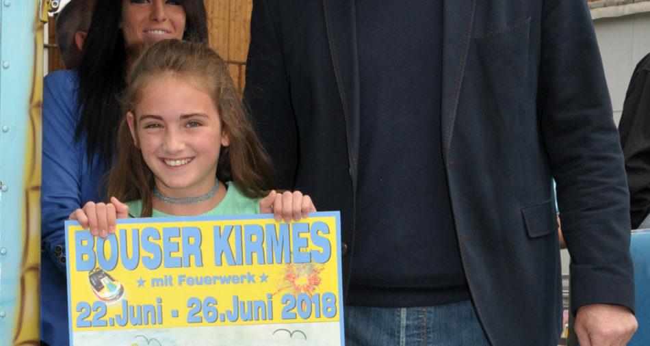 zu sehen ist die Schuelerin Emily Qehaja mit ihrem Gewinnerplakat aus dem Vorjahr und Buergermeister Stefan Louis